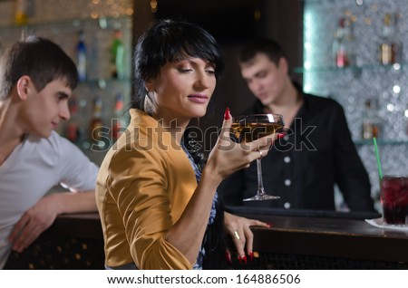Attractive young couple drinking at a pub counter enjoying themselves during Happy Hour as they relax and unwind after a days work