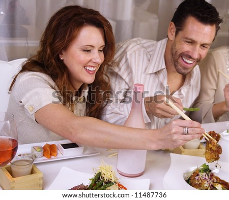 Attractive young couple eating sushi.