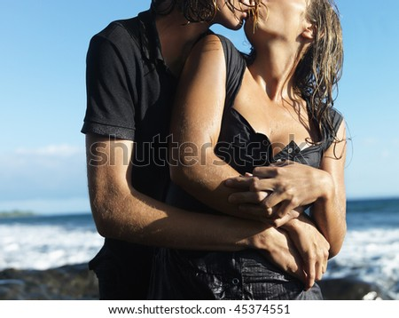 Attractive young couple embracing and kissing each other while standing on rocky coast. Horizontal shot.