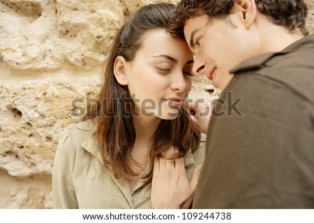 Attractive young couple having a romantic moment and leaning on a texture wall while on holidays.