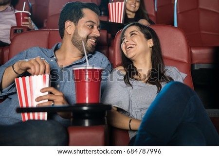 Attractive young couple having fun and enjoying the movie during a date at the cinema theater
