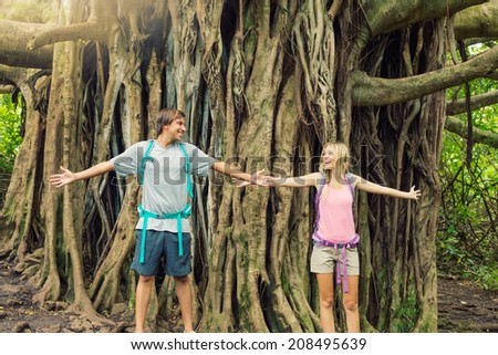 Attractive young couple having fun together outdoors on hike, standing in front of giant banyan tree. #208495639