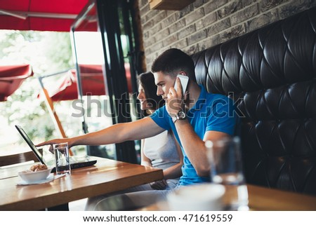 Attractive young couple having good time in cafe restaurant. They doing something on notebook while young man talking on his cellphone.