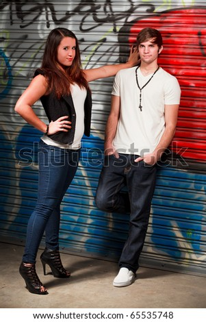 Attractive young couple in an urban fashion lifestyles setting with a graffiti background.