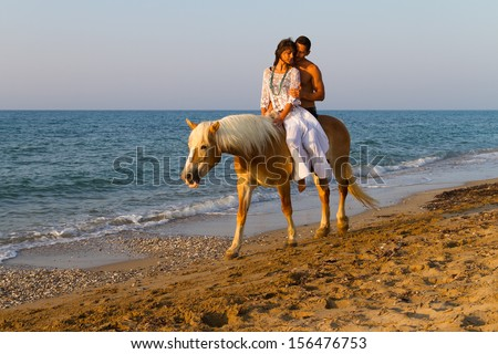 Attractive young couple in love, takes a romantic horse ride along a sandy shoreline in late afternoon summer sun.
