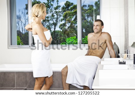 Attractive young couple in stylish twin bathroom