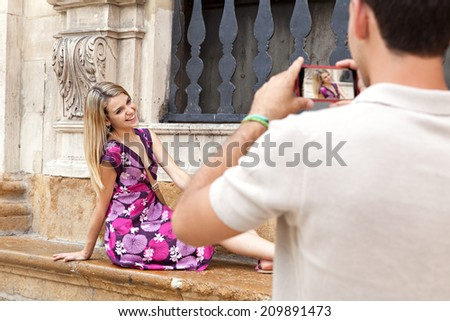 Attractive young couple on holiday, visiting a destination city and taking pictures with a smartphone, outdoors. Travel and technology lifestyle.