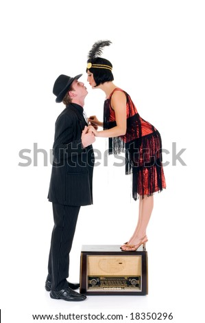 Attractive young couple, retro look with old radio.    Studio shot, white background.