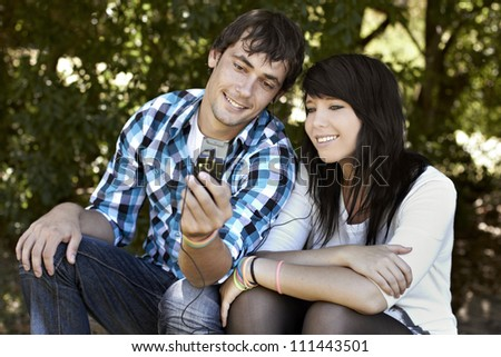 Attractive young couple sharing and listening to music while smiling