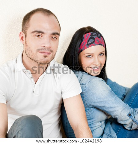 Attractive young couple sitting in their home
