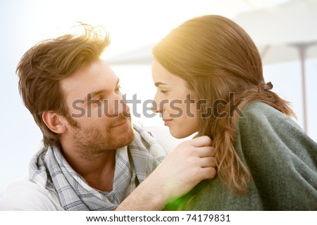 Attractive young couple sitting on beach kissing in summer sunset.?