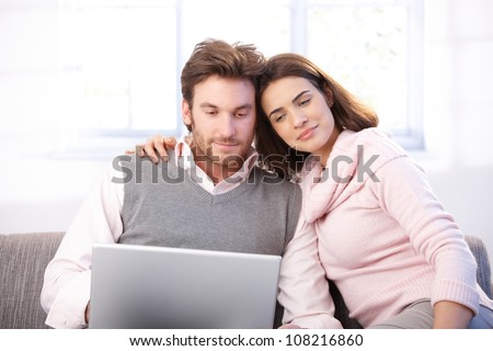 Attractive young couple sitting on sofa at home, embracing, using laptop, smiling.