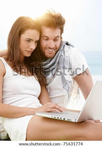 Attractive young couple sitting on the beach using laptop outdoor in summer sunlight, smiling.?