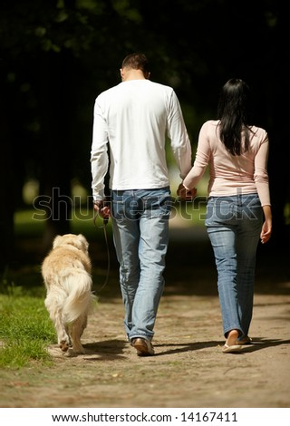 Attractive young couple spending time together outdoors walking with dog holding hands