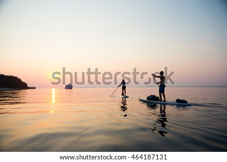 Attractive Young couple Stand Up Paddle Boarding, active beach lifestyle #464187131