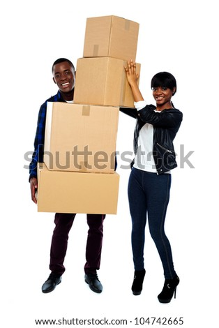 Attractive young couple standing with cardboard boxes. Smiling at camera