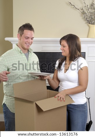 Attractive Young Couple Unpacking Dishes In Their New Home