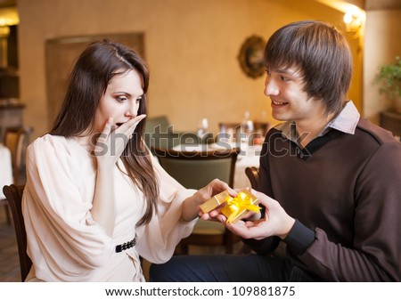 Attractive young couple with a gift in hands at restaurant