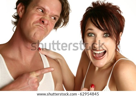 Attractive young couple with different emotions. Man angry woman laughing.  Over white background.