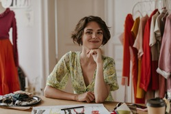 Attractive young curly short-haired woman in floral dress smiles and looks into camera. Portrait of fashion designer in office.