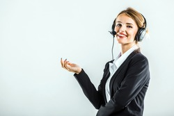 Attractive young dark hair caucasian callcenter operator, in a white blouse and a black jacket, is talking on the headset, in the white isolated background