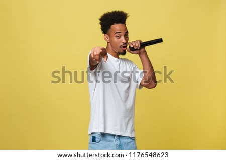 Attractive young dark-skinned man with afro haircut in white t shirt, gesticulating with hands and microphone, dancing and singing on party, having fun.