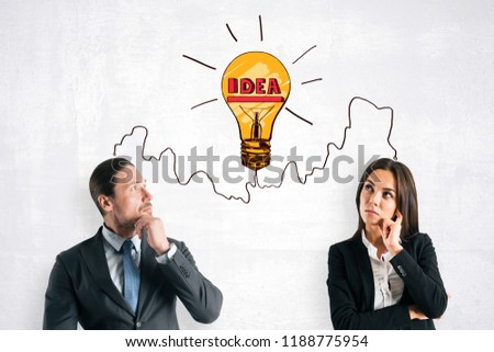 Attractive young european businessman and woman standing on concrete background with lamp sketch. Idea and innovation concept