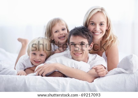 Attractive young family with children in the bedroom