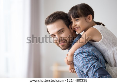 Attractive young father standing in living room holds on back adorable daughter at home. Smiling daughter spend time with loving father playing piggyback her daddy. Family leisure activities concept