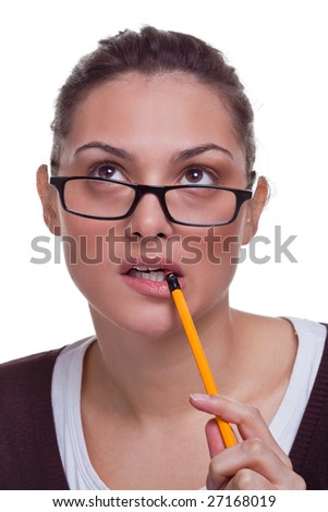 Attractive young female chewing a pencil as she thinks about something, white background.