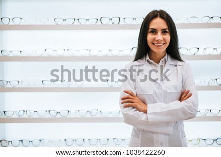 Attractive young female doctor in ophthalmology clinic. Doctor ophthalmologist is standing near shelves with different eyeglasses.