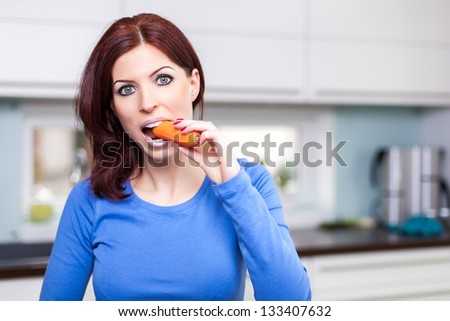 Attractive young female eating carrot in the kitchen