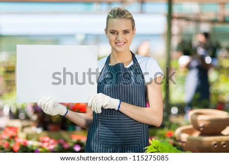 attractive young female florist holding white board in greenhouse