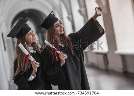 Attractive young female graduates in academic dresses are holding diplomas, doing selfie and smiling while standing in university hall