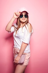 Attractive young female in stylish outfit touching cap and looking up while standing on pink background