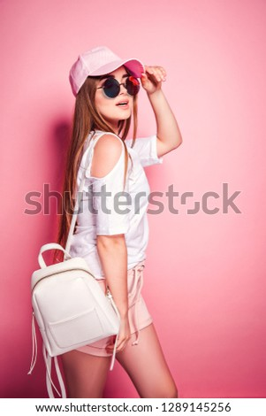 Attractive young female in stylish outfit touching cap and looking up while standing on pink background #1289145256