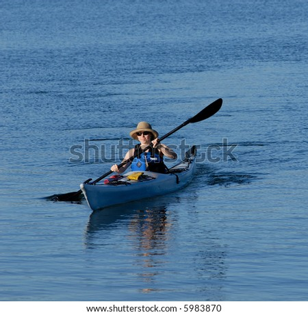 Attractive young female kayaker is rowing in deep blue sub-tropical waters of Mission Bay, San Diego, California.