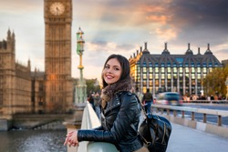 Attractive, young, female London traveler tourist enjoys the view to the Westminster Palace and Big Ben clocktower touring a sightseeing city trip