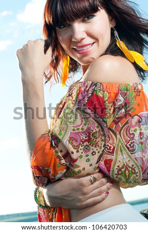 Attractive young female posing outdoors, smiling and looking at camera