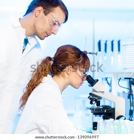 Attractive young female research scientist and her post doctoral male supervisor looking at the microscope slide in the life science (forensics, microbiology, biochemistry, genetics, ) laboratory.