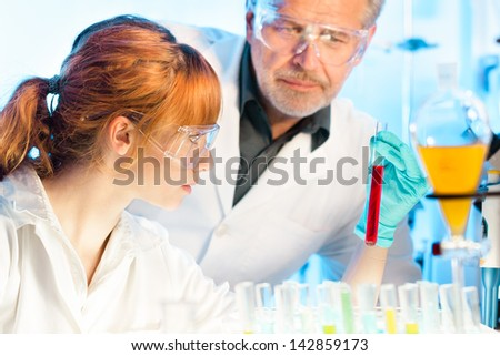 Attractive young female scientist and her senior male supervisor observing color shift of a red liquid in the glass tube in the life science research laboratory (biochemistry, genetics, forensics,..)