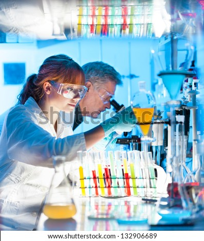 Attractive young female scientist and her senior male supervisor pipetting and microscoping in the life science research laboratory (biochemistry, genetics, forensics, microbiology..)