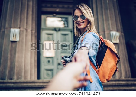 Attractive young female tourist is exploring new city. Follow me! In search of new adventures!