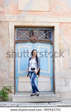 Attractive young female tourist near the old building.
