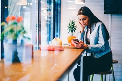 Attractive young female watching video online on smartphone spending free time in cafe interior, hipster girl chatting with boyfriend sending text messages using cheap mobile tariffs for SMS