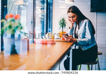 Attractive young female watching video online on smartphone spending free time in cafe interior, hipster girl chatting with boyfriend sending text messages using cheap mobile tariffs for SMS #749804236