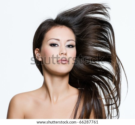 Attractive young female with beautiful long brown hairs, posing isolated on white