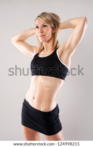 Attractive young fit woman isolated on grey background