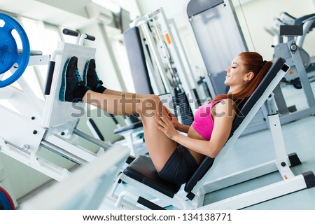 Attractive young fitness model works out on training apparatus inside in fitness center