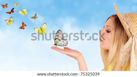 Attractive young girl blowing on butterflies.